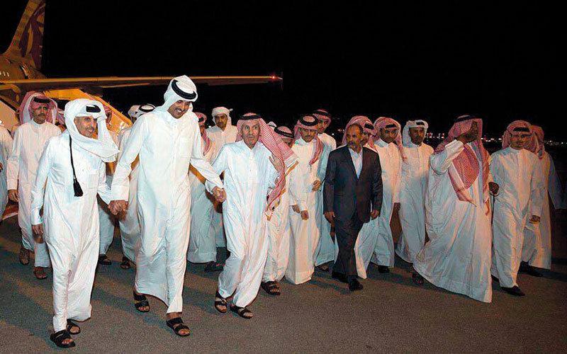 تميم بن حمد يحتفل مع الرهائن بعد وصولهم إلى مطار حمد إثر نجاح «صفقة المليار». أرشيفية