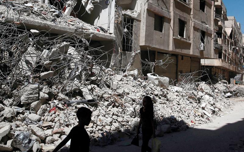 طفلان يمرّان وسط الدمار في غوطة دمشق الشرقية. رويترز