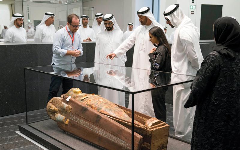 محمد بن راشد ومحمد بن زايد يستمعان إلى شرح حول إحدى معروضات المتحف. وام