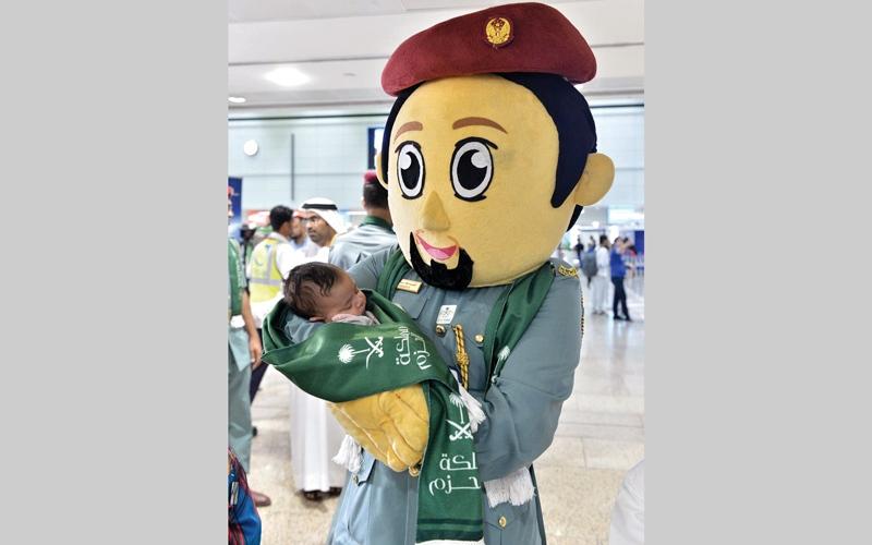 الصورة: شرطي يرتدي زياً محبباً للأطفال وهو يحتضن رضيعاً سعودياً لدى وصوله إلى مطار دبي