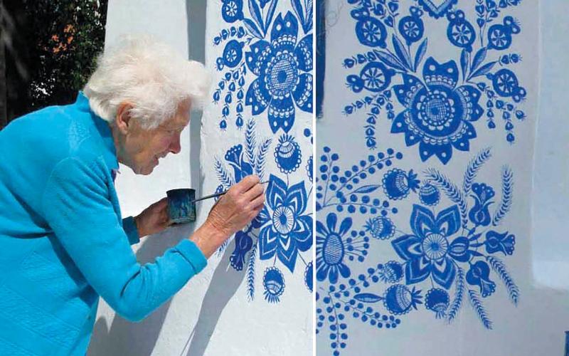 الصورة: تسعينية تقضي وقت فراغها في تزيين جدران قريتها