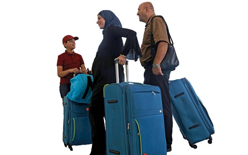 عائلة كردية تبدو في عجلة من أمرها للّحاق برحلة الطائرة قبل بدء سريان الحظر الجوي الدولي من وإلى الإقليم. إي.بي.إيه