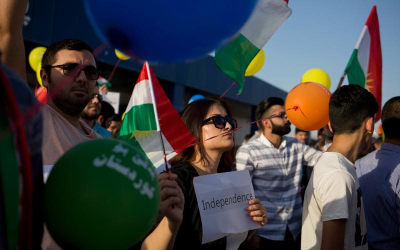 سيدة كردية تحمل لافتة كتب عليها «استقلال» خلال الاحتفال بنتيجة الاستفتاء  الذي نظّم في إقليم كردستان العراق أخيراً.  أ.ب