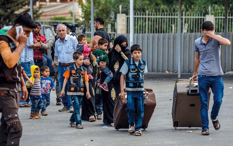 سوريون يهرعون خارج سورية عبر الحدود التركية. أ.ف.ب