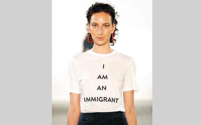 عارضة أزياء تستعرض تي شيرت كتب عليه «أنا مهاجر». غيتي