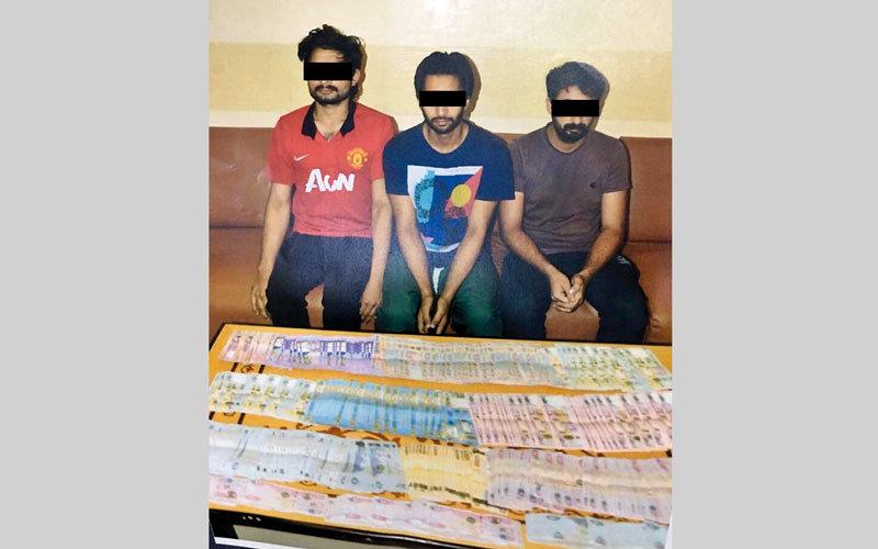3 متهمين وأمامهم جانب من المسروقات. من المصدر