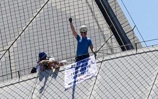 الصورة: ناشطون يرفعون لافتة تحمل عبارة «أستراليا الرائدة عالمياً في القسوة» أعلى دار أوبرا سيدني
