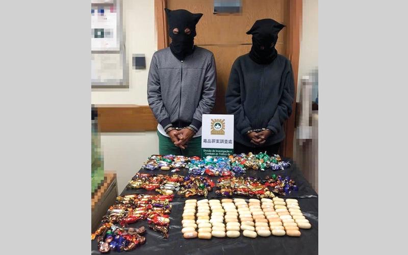 متهمان وأمامهما جانب من المخدرات المعدة للترويج. من المصدر