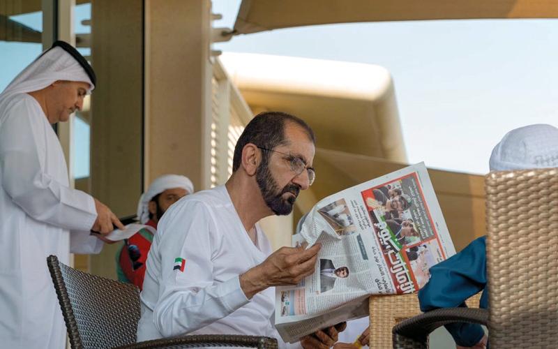 """الصورة: محمد بن راشد يقرأ """"الإمارات اليوم"""" خلال حضوره إحدى الفعاليات الرياضية في دبي"""