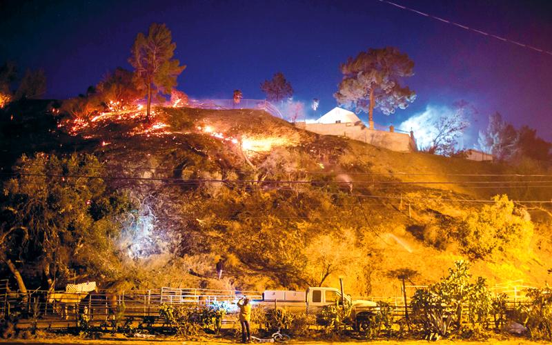 سيدة تلتقط صوراً للحريق الذي غطى مساحات شاسعة.  أ.ف.ب