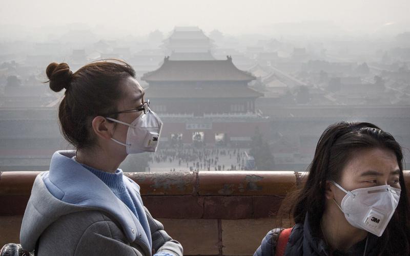 سيدتان تغطيان وجهيهما بقناعين اتقاءً لآثار التلوث المستمرة في بكين.  غيتي