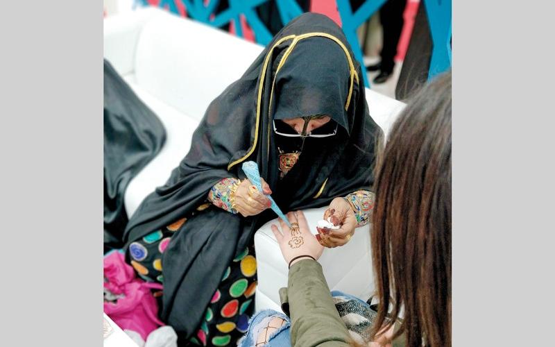 الصورة: فرنسيات يلبسن البرقع الإماراتي ويرسمن بالحناء