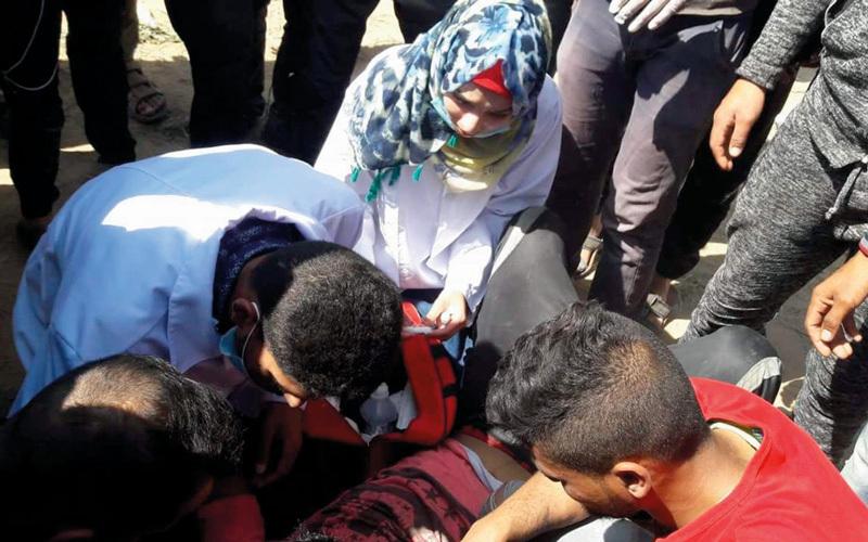 الشابة المسعفة رزان النجار خلال مشاركتها طواقم الإسعاف في إنقاذ المصابين على الشريط الحدودي. الإمارات اليوم