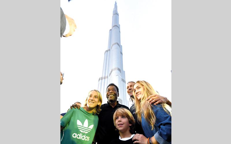 الأسطورة البرازيلي بيليه في صورة تذكارية مع النجم الإسباني سالغادو وأبنائه أمام برج خليفة. تصوير: باتريك كاستيلو