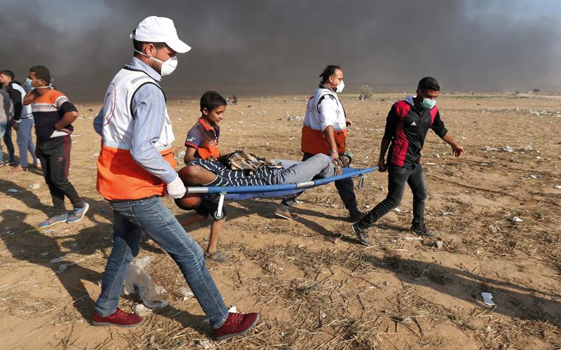 نشطاء يجلون أحد الجرحى الذي أصيب خلال المواجهات. رويترز