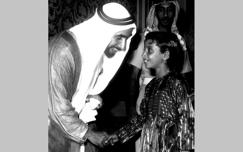 المغفور له الشيخ زايد بن سلطان آل نهيان، طيب الله ثراه، يصافح فتاة صغيرة.