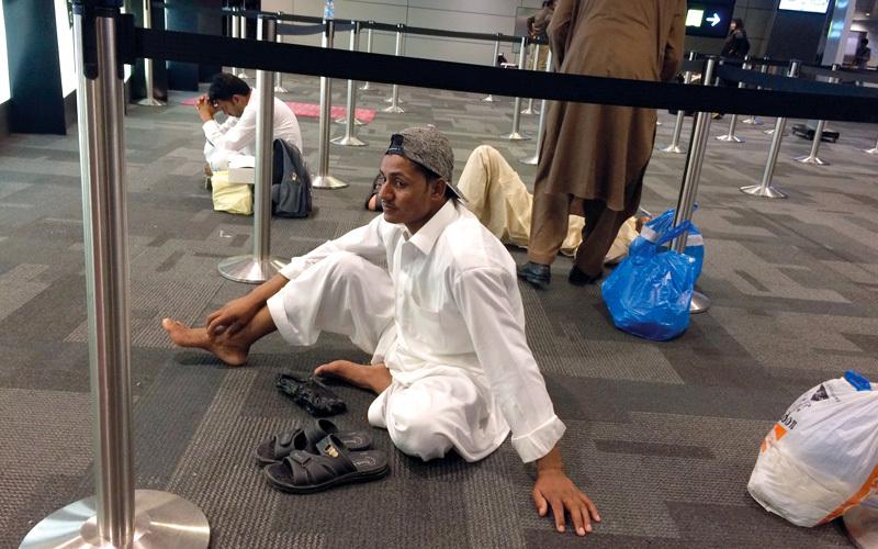 مسافر افترش الأرض بعد أن تقطعت به السبل نتيجة إلغاء رحلته على الخطوط الجوية القطرية التي تضررت بسبب المقاطعة. أرشيفية