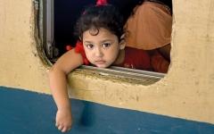 الصورة: طفولة: طفلة تطل من نافذة القطار في بنغلاديش.
