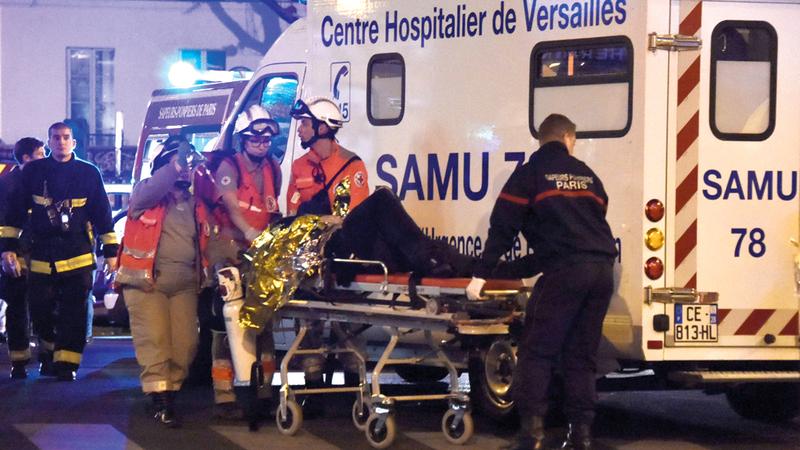 مجموعة من رجال الإنقاذ يجلون أحد الجرحى بعد هجوم إرهابي نفذه «داعش» في وسط باريس. أ.ف.ب