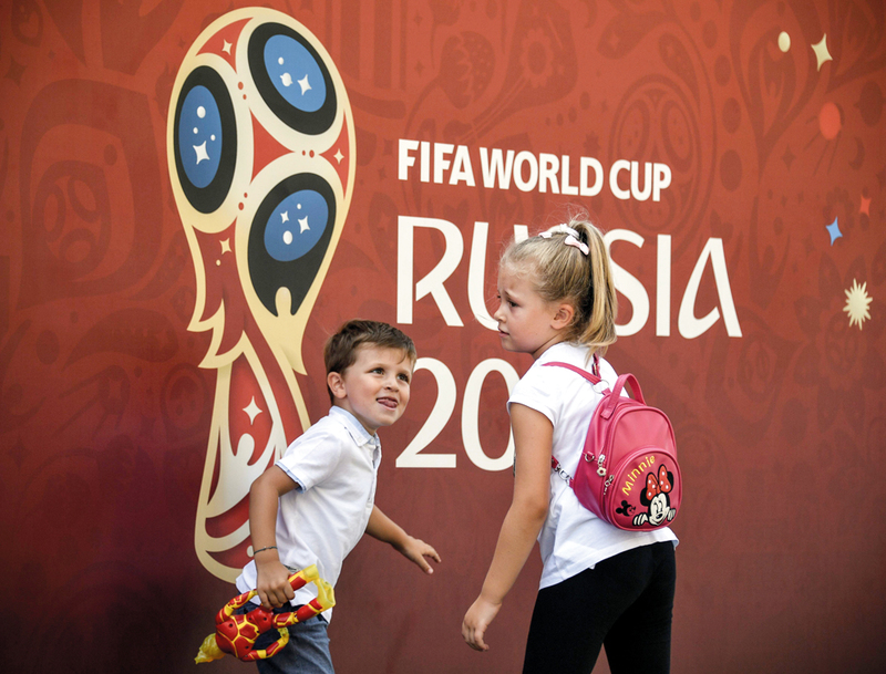 طفلان يمرّان أمام ملصق لكأس العالم في موسكو بروسيا. أ.ف.ب