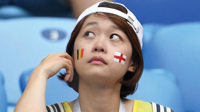 مشجعة ترسم علمي إنجلترا وبلجيكا خلال وجودها في مدرجات ملعب سانت بطرسبرغ لمتابعة مباراة المركز الثالث.  أ.ف.ب