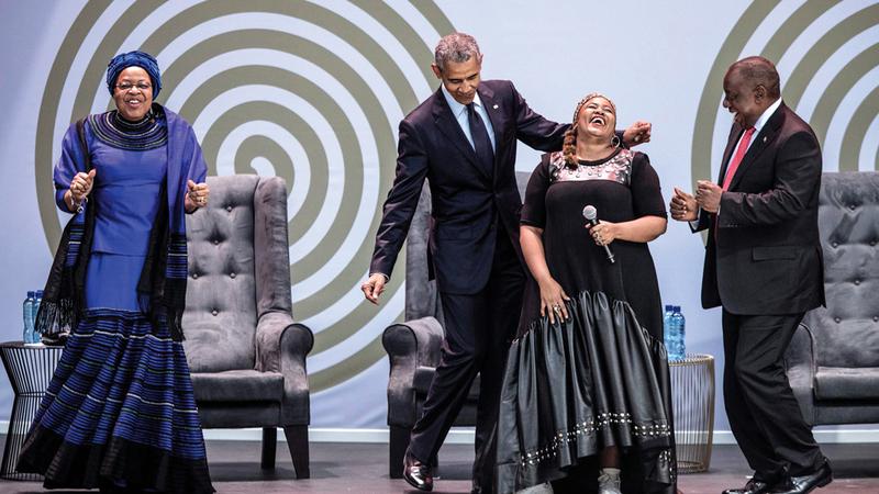 أوباما وأرملة مانديلا غراسا ميشيل «إلى اليسار» ورئيس جنوب إفريقيا رامافوسا يغنون ويرقصون أثناء الاحتفال بذكرى ميلاد الزعيم نيلسون مانديلا.  أ.ف.ب