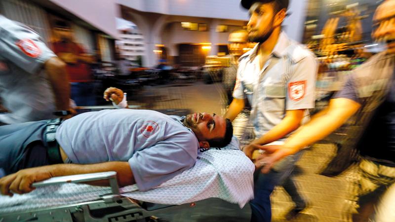 أحد الجرحى الفلسطينيين خلال نقله إلى مستشفى الشفاء في غزة.  أ.ف.ب