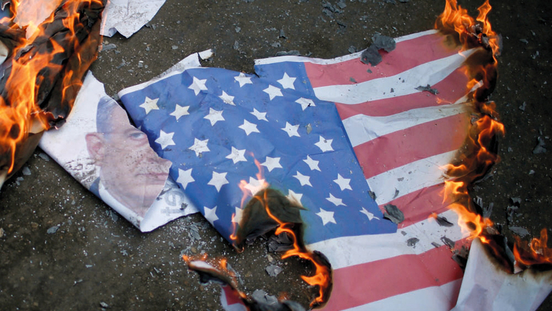 متظاهرون يحرقون العلم الأميركي وصورة لنتنياهو أثناء تظاهرة في غزة. أرشيفية