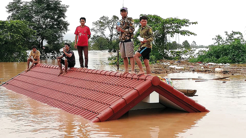 قرويون يعتلون أسقف بيوتهم للنجاة من المياه التي غمرت مقاطعة أتابيو.  أ.ف.ب