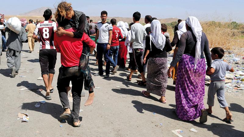 أيزيديون يعبرون الحدود العراقية السورية هرباً من القتال في شمال العراق. أ.ب