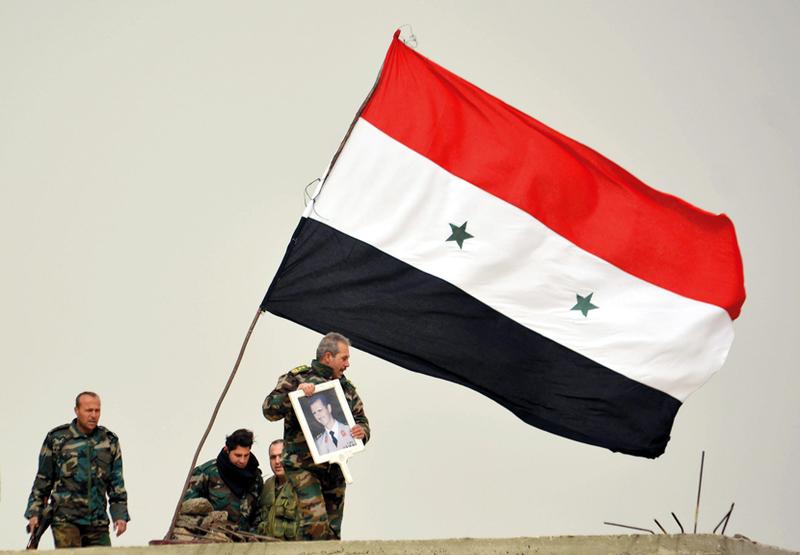 قوات النظام السوري ترفع رايتها فوق مدينة درعا جنوب سورية احتفالاً بانتصارها.  رويترز