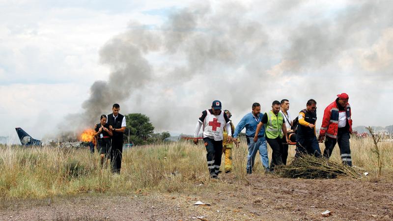 أعمدة الدخان تتصاعد في الحقل الذي انزلقت فيه الطائرة.  أ.ب