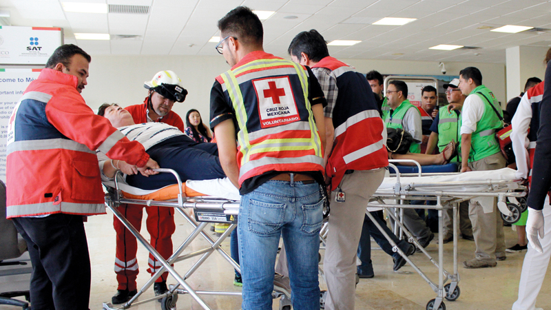 رجال الصليب الأحمر يجلون الجرحى من الموقع.  أ.ب