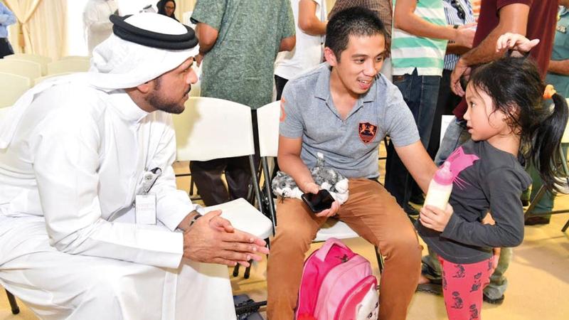 نائب مدير الإدارة العامة للإقامة وشؤون الأجانب في دبي يتحدث مع طفلة قدمت مع والدها. تصوير أحمد عرديتي