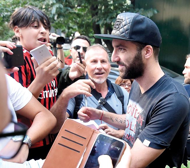 هيغواين خلال وصوله إلى ميلان محاطاً بمشجعي أنصار «الروسينيري». رويترز