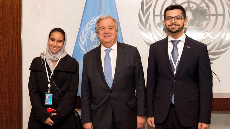 الأمين العام للأمم المتحدة أنطونيو غوتيريس متوسطاً ممثلَين من برنامج الإمارات للمندوبين الشباب. من المصدر