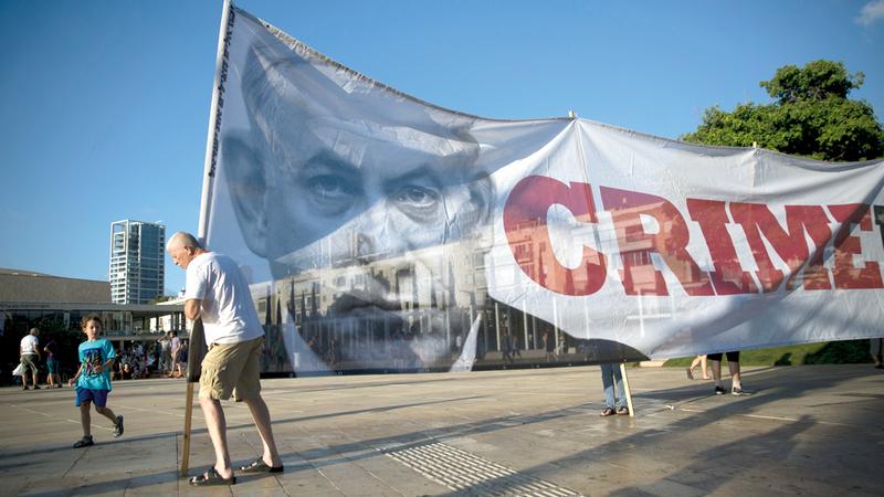 أحد الإسرائيليين يحمل لافتة كبيرة عليها صورة رئيس الوزراء بنيامين نتنياهو احتجاجاً على قانون يهودية الدولة. أ.ب
