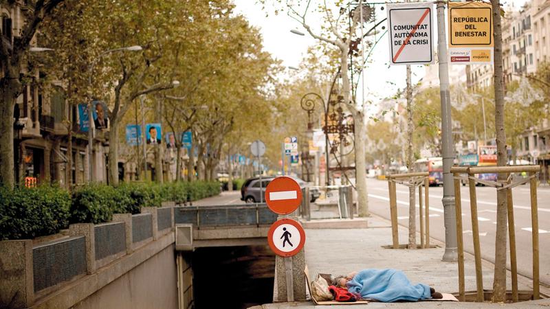 مشرد ينام على رصيف أثناء الانتخابات العامة الإسبانية في برشلونة شتاء 2011. غيتي