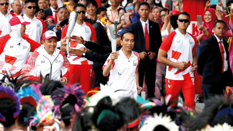 الرئيس الإندونيسي جوكو ويدودو يحمل الشعلة الأولمبية أمس. رويترز