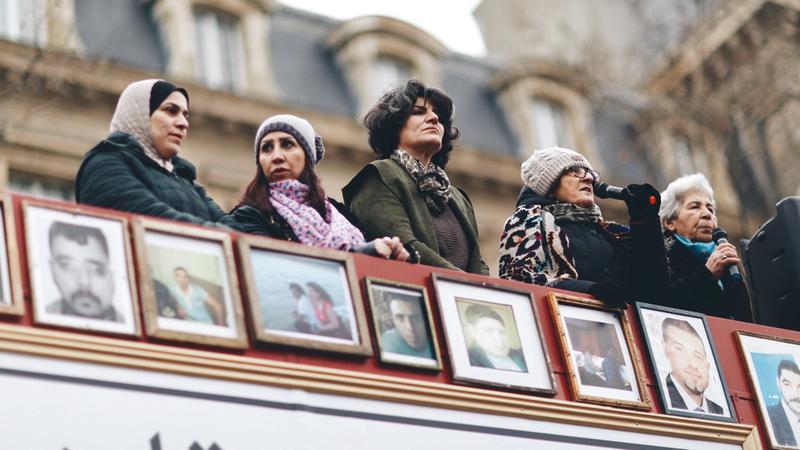 ناشطون بجانب صور نشطاء معتقلين في سجون النظام السوري. أرشيفية
