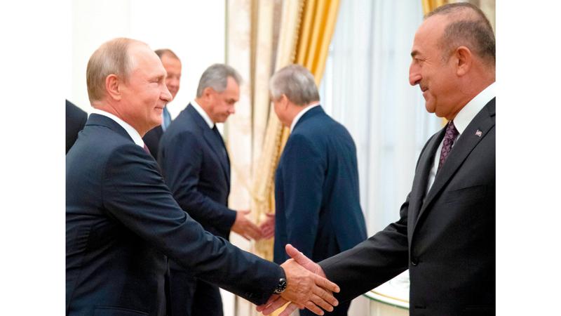 الرئيس الروسي يصافح وزير الخارجية التركي في موسكو. أ.ف.ب