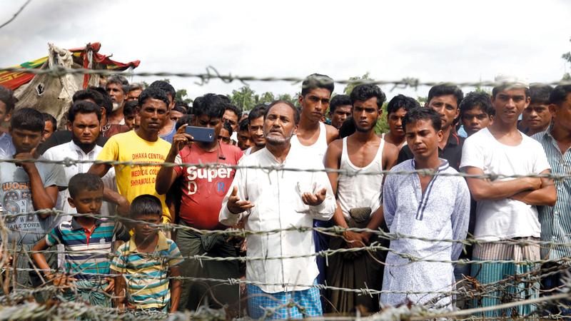 لاجئون يتجمعون في الأرض المحايدة خلف سياج على الحدود بين ميانمار وبنغلاديش. إي.بي.إيه
