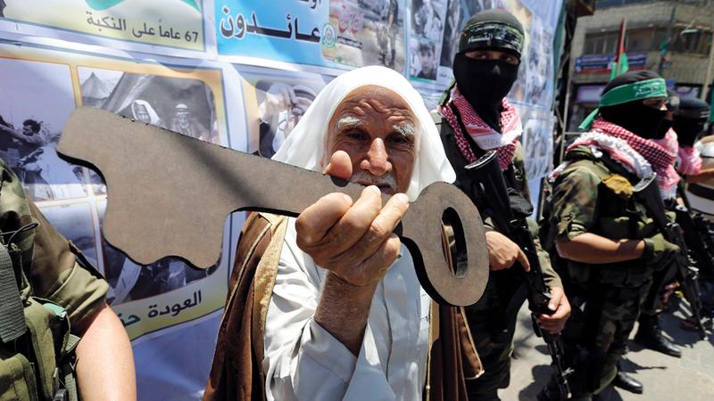 فلسطيني يمسك بمجسم مفتاح تأكيداً لحق العودة خلال مسيرة في رفح.  أرشيفية