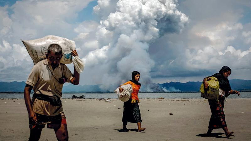نازحون من الروهينغا يسيرون في جو ملبد بالغيوم. رويترز