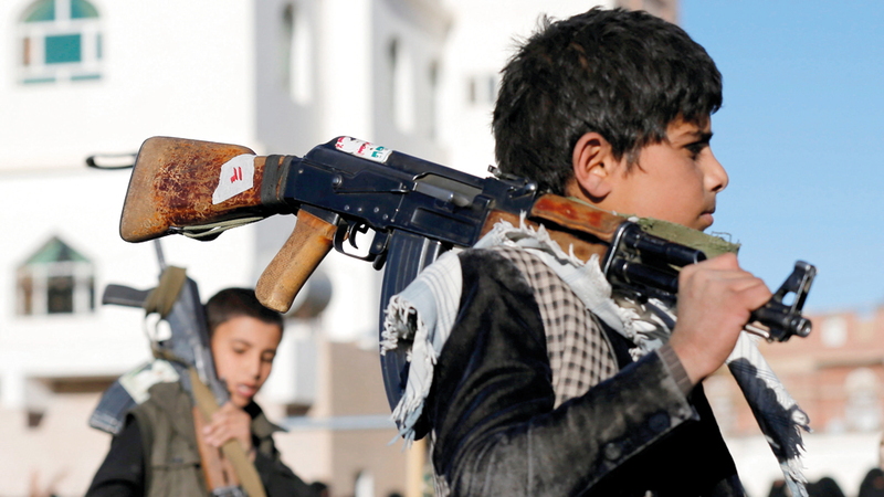طفلان يحملان سلاحاً خلال تجمُّع حوثي بصنعاء في انتهاك واضح لحقوق الإنسان.  رويترز - أرشيفية