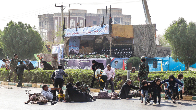 جنود إيرانيون وأشخاص على الأرض بعد الهجوم على العرض العسكري في الأحواز. أ.ف.ب