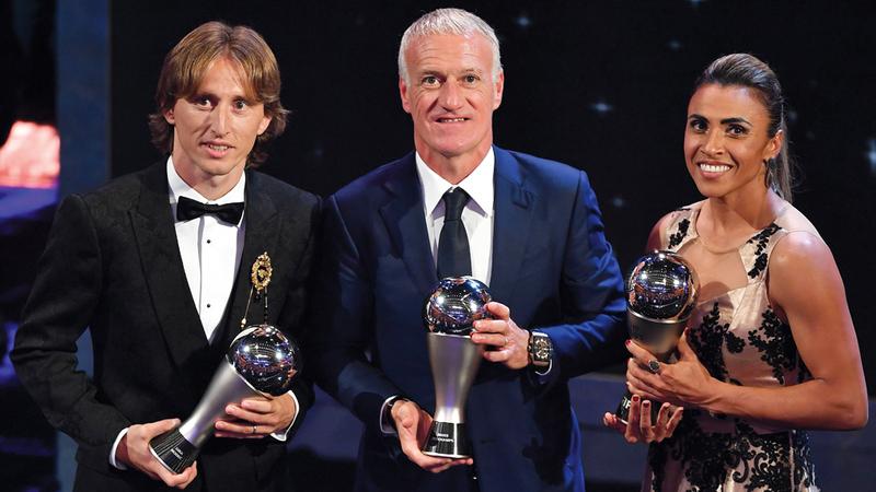 مودريتش خلال فوزه بجائزة أفضل لاعب، وديشامب أفضل مدرب، والبرازيلية مارتا أفضل لاعبة. أ.ف.ب