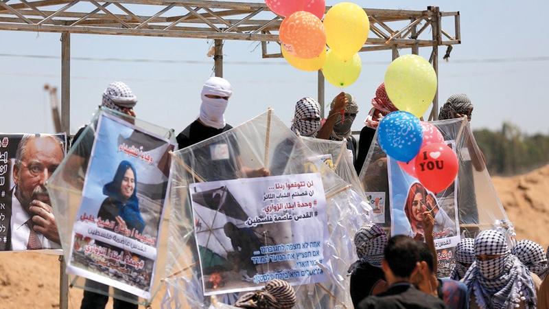 شباب وحدة البالونات الحارقة يغمسون قطع قماش بالوقود لإشعال البالونات قبل إطلاقها إلى الأراضي المحتلة. الإمارات اليوم