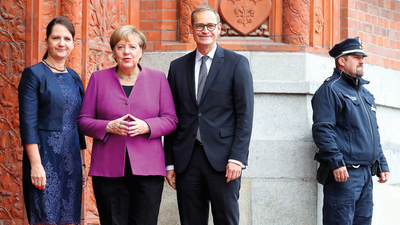المستشارة الألمانية أنغيلا ميركل في لقطة تذكارية مع رئيس البرلمان الألماني مايكل موللر أمام مقر بلدية برلين قبل الاحتفال الرسمي بيوم الوحدة في برلين. إي.بي.إيه