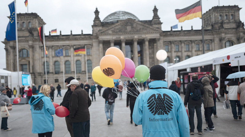 رجل يوزع بالونات رسم عليها شعار النسر الألماني مجاناً في ذكرى يوم وحدة ألمانيا.  إي.بي.إيه